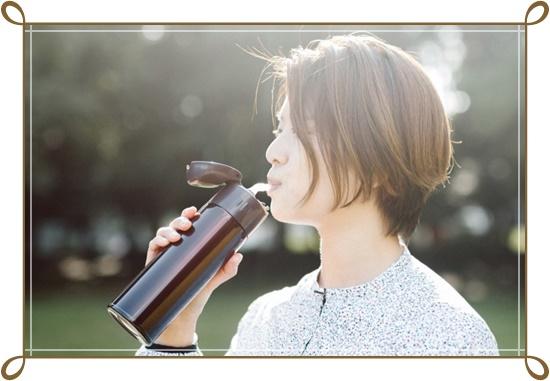水筒から飲み物を飲む女性の画像