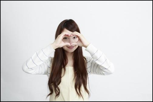 ハートのポーズをする女性の画像