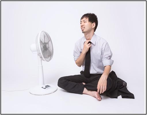 扇風機で涼んでいるサラリーマン画像