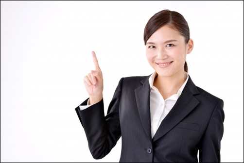 スーツ姿で指差しする笑顔の女性画像