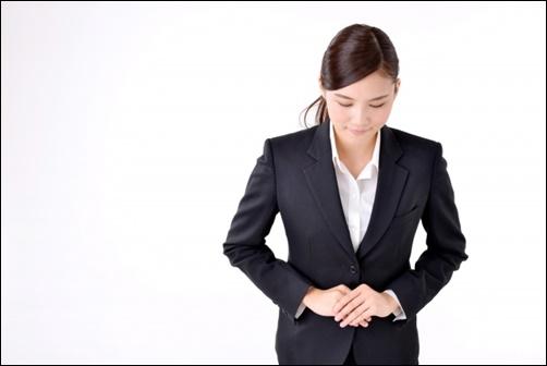 お辞儀をするスーツ姿の女性画像