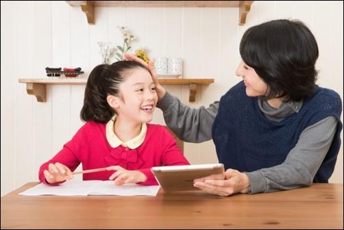 お母さんに勉強を褒められる小学生の女の子の画像