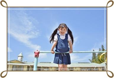 女の子の幼稚園生が鉄棒をしている画像