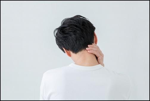 首を押さえる男性の画像