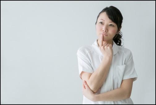 白衣を着て考える女性の画像