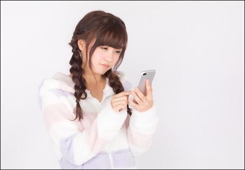 不安そうに電話を見つめる女性の画像